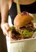 Waitress holding big hamburger