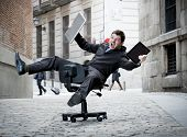 foto of slave  - Happy crazy business man rolling downhill on chair with computer and tablet - JPG