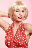 Pinup Girl In Blond Wig And Retro Red Dress Winking. Vintage.