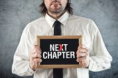 Businessman Holding Blackboard With Next Chapter Title