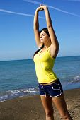 Beautiful Sporty Woman Stretching And Relaxing With Music On The Beach