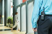 picture of policeman  - security guard controlling indoor entrance gate  - JPG