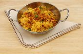 stock photo of biryani  - Lamb biryani in a balti dish with a serviette on a wooden table top - JPG
