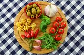 Italian ingredients on wooden board on checkered tablecloth