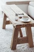 Still life details, cup of coffee on rustic bench on white carpet