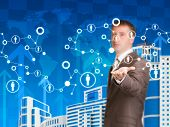 Businessman with skyscrapers and network