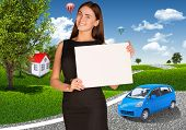 Businesswoman with small car, houses and trees