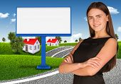 Businesswoman with empty billboard, trees and houses
