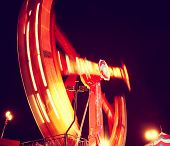 a fair ride shot with a long exposure at night toned with a retro vintage instagram filter  effect