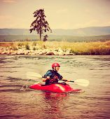 a woman kayaking on a rough river during summer toned with a retro vintage instagram filter  effect