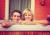 a young couple sitting in hot tub toned with a retro vintage instagram filter