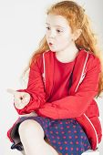 Pointing Little Red-haired Caucasain Girl With Surprised Expression