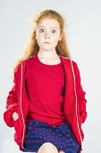 Portrait Of Surprised Redhaired Caucasian Little Girl In Red Jacket And Polka Dotted Skirt