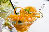 Fresh Orange and lime Mojito over white background