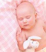 Cute baby asleep in pink bedroom, relaxing in the bed, adorable healthy child dreaming, safe childho
