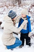 Family of mother and her adorable little daughter outdoors on beautiful winter day with snow