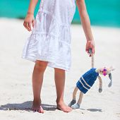 Little girl with her bunny toy enjoying tropical beach vacation