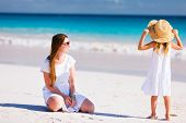 Young mother and her adorable little daughter on summer beach vacation