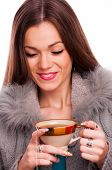 Young brunette with close eyes, holding a cup of hot tea - isolated on white