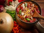 stock photo of chili peppers  - Spicy bowl of chili surrounded by fresh onion - JPG