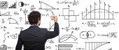 Young businessman writing math formulas