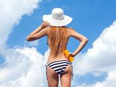 Sun protection and summer body care concept, woman wearing hat and bikini holding sunscreen spf loti