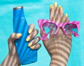 Summer fashion and beauty hand care concept, woman holding sunglasses and sunscreen lotion
