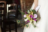 Bride holding beautiful wedding bouquet of orchid and calla
