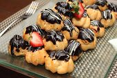 stock photo of eclairs  - Eclair with hot chocolate fudge on food table - JPG