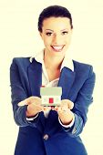 Beautiful young businesswoman holding house model over white - real estate loan concept
