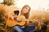 beautiful girl playing the guitar in a wheat field