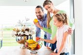 Mother, father, child picking fresh fruits for healthy living in home kitchen