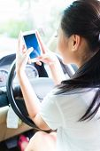 Asian young woman texting message on mobile phone or smartphone while driving car