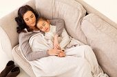 cute mother and her little girl sleeping on the couch
