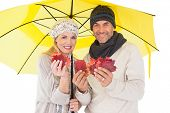 Couple in winter fashion showing autumn leaves under umbrella on white background