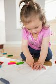 Little girl drawing in the living room at home