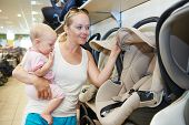 woman choosing child car seat with little baby in shop supermarket
