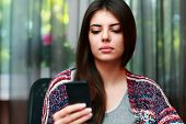 Serious beautiful woman using smartphone at home