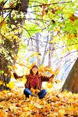 Happy young woman throwing autumn leaves in park.