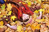 Girl lying in autumn leaves portrait, outdoor.