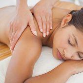 Beautiful brunette enjoying a shoulder massage at the health spa