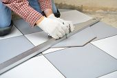 Tiler marks the tile during the floor installation
