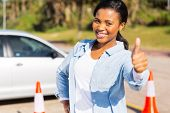stock photo of driving school  - happy young african girl standing in driving school giving thumb up - JPG