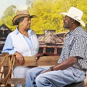 A mature, senior African American couple flirting over a fence in an old western town.