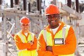 picture of substation  - handsome young african american electrical engineer with arms crossed in substation - JPG