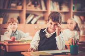 Little schoolboy  sitting behind school desk during lesson in school