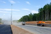 pic of sweeper  - Street sweepers with clouds of dust at the road construction - JPG
