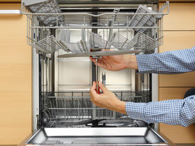 picture of handyman  - handyman repairing a dishwasher with screwdriver  - JPG