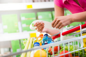 image of grocery cart  - Unrecognizable woman checking a long grocery receipt leaning to a full shopping cart at store - JPG