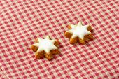 two christmas star cookies on checkered tablecloth